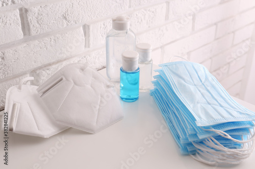 Hand sanitizers and respiratory masks on table near white brick wall. Protective essentials during COVID-19 pandemic