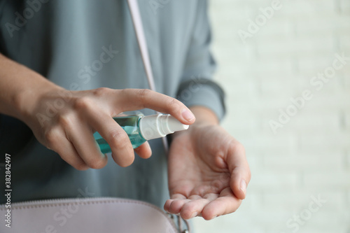 Woman applying hand sanitizer on light background, closeup. Personal hygiene during COVID-19 pandemic