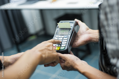 Fényképezés Waiter holds the card machine while the customer is dialing the code on the card reader to pay