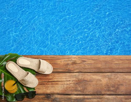 Fotografía Beach accessories on wooden deck near swimming pool, flat lay