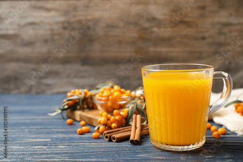 Fresh sea buckthorn tea on blue wooden table. Space for text