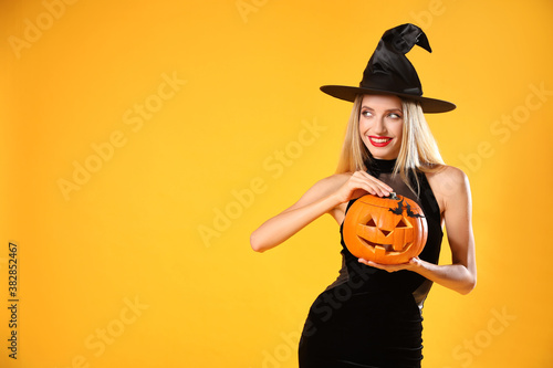 Valokuvatapetti Beautiful woman in witch costume with jack o'lantern on yellow background, space for text