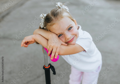 Photo Little girl with pigtails and hairpins on her hair, the child is resting, holding the wheel, after riding a scooter