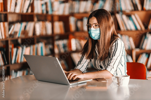 Young attractive female student with brown hair having face mask and using laptop while sitting in library Fototapeta