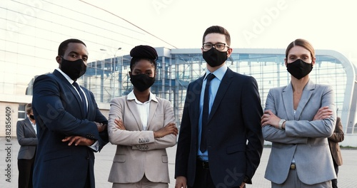 Fototapeta Portrait of mixed-races businessmen and businesswomen in masks and official style standing in urban city and looking at camera. Multi ethnic males and females business partners Men an women colleagues obraz
