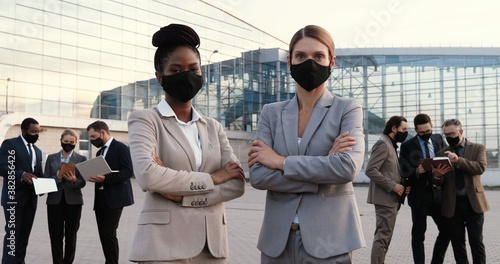 Portrait mixed-races young businesswomen in masks and official style standing posing to camera outdoor in city Wallpaper Mural
