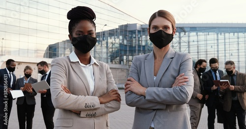 Portrait mixed-races young businesswomen in masks and official style standing posing to camera outdoor in city Canvas Print