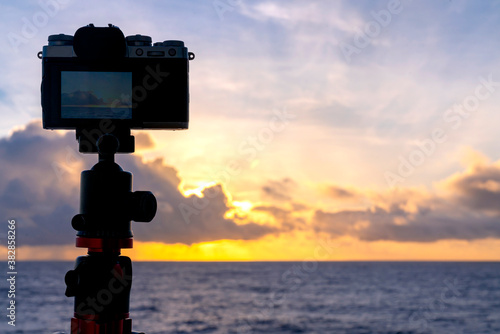 Fototapeta silhouette of mirrorless camera on tripod shooting beautiful calm sea with sunshine reflection on water at sunrise or sunset free copy space for your text obraz