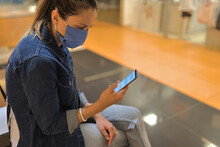 Woman In Protective Mask Sit On Bench In Shopping Center And Look At Phone. Empty Hall In Trading Floor, Showcases With Manikin.
