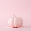 Pink pumpkin on a pastel pink background. Minimal Halloween concept.