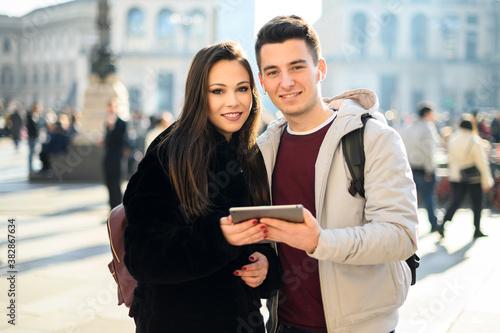 Young couple using a digital tablet outdoor while visiting a city Billede på lærred