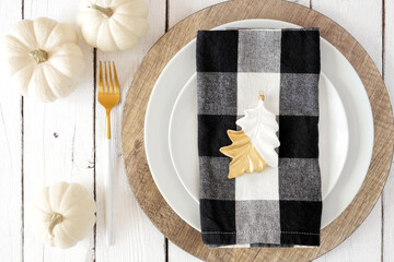 Autumn harvest or thanksgiving dinner table setting with plates, fork, buffalo plaid napkin and white pumpkins. Above view close up on a white wood background.