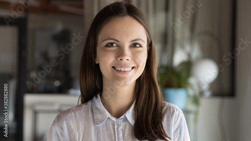 Head shot close up portrait of young european ambitions female employee. Profile photo of millennial beautiful businesswoman team leader, manager or company representative looking at camera.