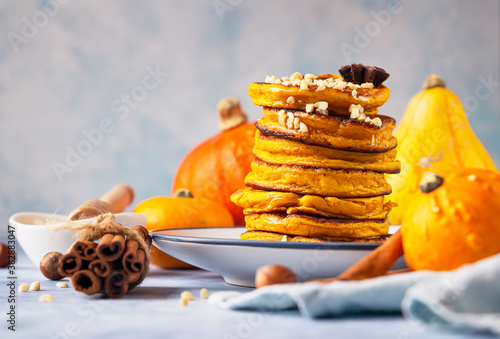 Fotografía Fluffy spicy pumpkin pancakes with honey and nuts, fresh pumpkins and spices on blue stone background