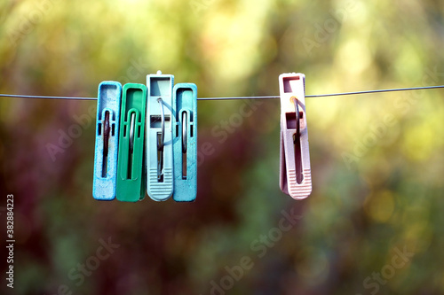 Fototapeta Old clothespins hang on the wire outdoor, blurred background, selective focus
