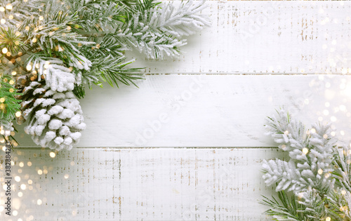 Fototapeta Christmas tree branch and pine cone in snow on a white wooden background. Winter festive concept. Flat lay, copy space. obraz