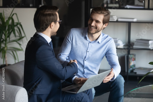 Fotografie, Tablou Smiling young male employee shaking hands with pleasant ceo executive manager, making agreement in modern office