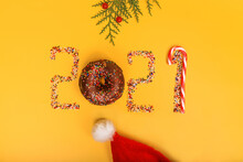 New Year 2021, Numbers From Pastry Sprinkles, Beads, Sweet Chocolate Donut And Red And White Lollipop, Green Branches, Santa Claus Hat On Yellow Background, Christmas Card, Holiday Food