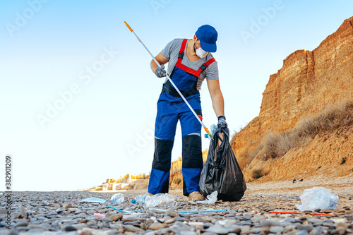 Man volunteer collecting garbage on the beach with a reach extender stick Wallpaper Mural