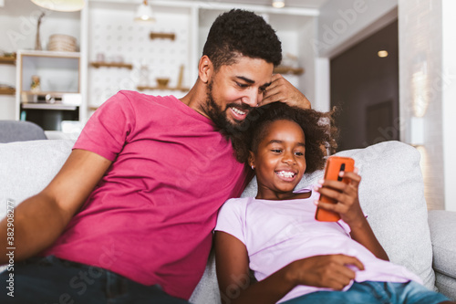 Canvastavla African american father and daughter with smartphone at home