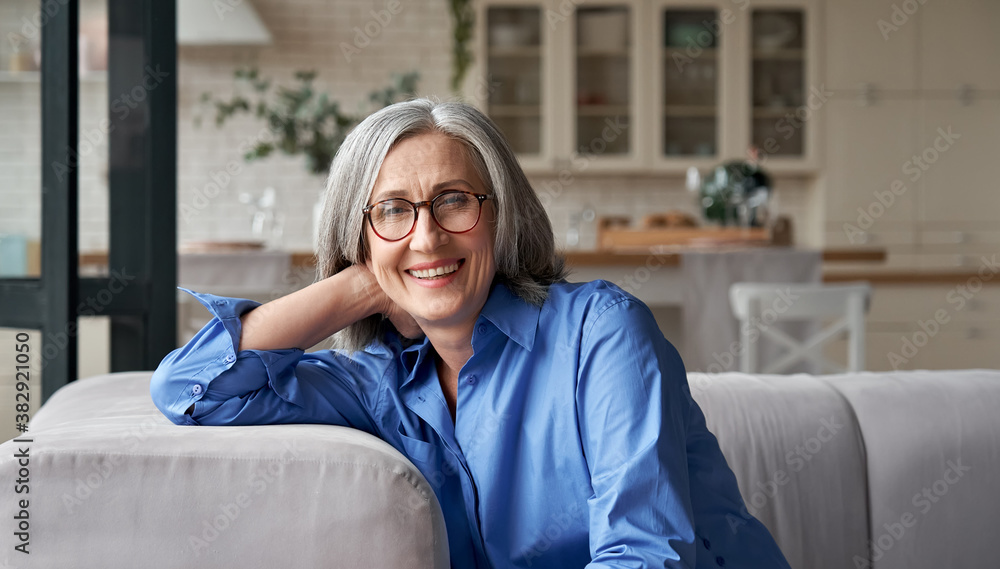 Fototapeta Happy relaxed mature old adult woman wearing glasses resting sitting on couch at home. Smiling middle aged grey-haired elegant senior lady relaxing on comfortable sofa looking at camera. Portrait.
