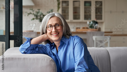 Obraz Happy relaxed mature old adult woman wearing glasses resting sitting on couch at home. Smiling middle aged grey-haired elegant senior lady relaxing on comfortable sofa looking at camera. Portrait. - fototapety do salonu