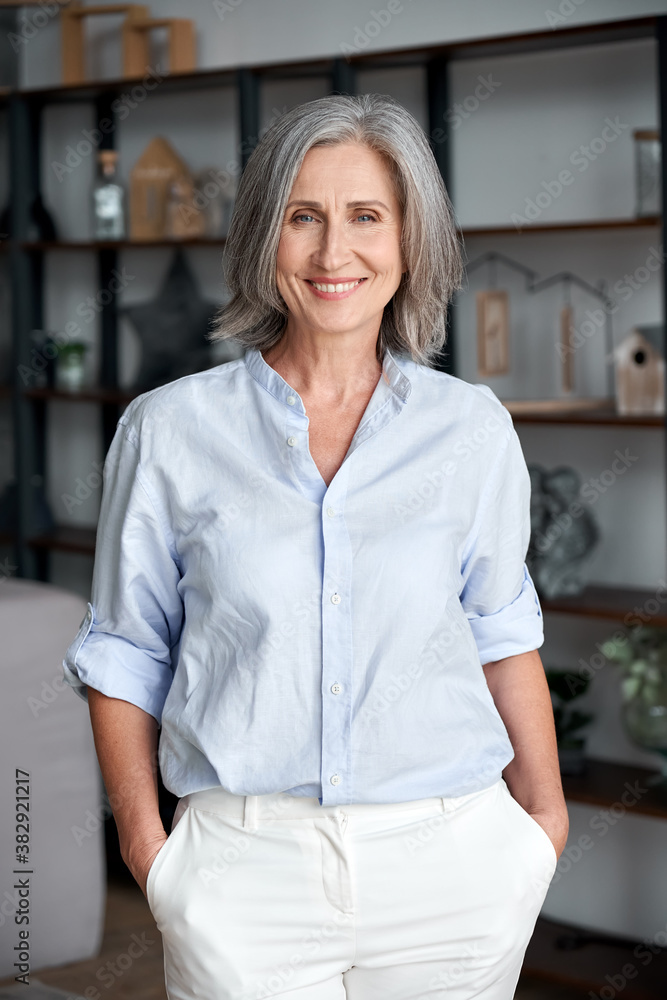Fototapeta Smiling confident stylish mature middle aged woman stand at home office. Old senior elegant businesswoman, 60s gray-haired lady executive business leader manager looking at camera, vertical portrait.