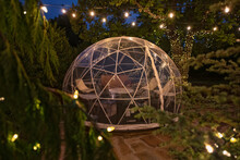 Individual Tent Igloo With Vintage Lighting Overhead As A Place To Eat Dinner