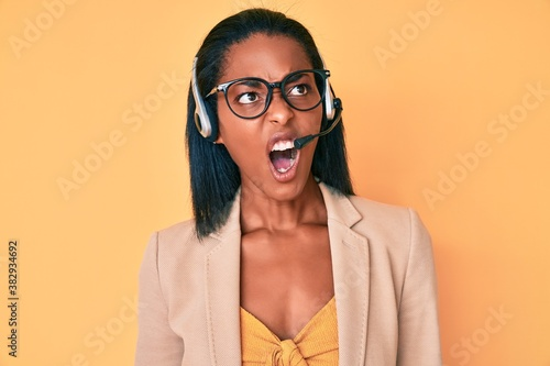 Obraz na plátně Young african american woman wearing call center agent headset angry and mad screaming frustrated and furious, shouting with anger