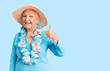 Leinwandbild Motiv Senior beautiful woman with blue eyes and grey hair wearing summer hat and hawaiian lei smiling happy and positive, thumb up doing excellent and approval sign