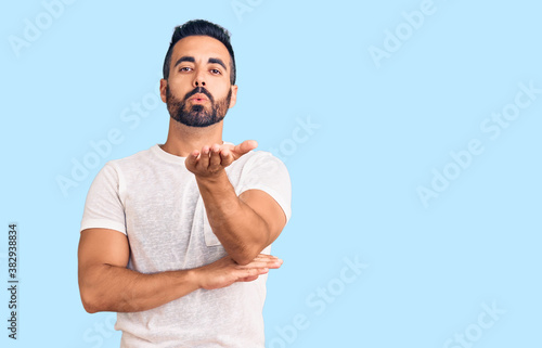 Fototapeta Young hispanic man wearing casual clothes looking at the camera blowing a kiss with hand on air being lovely and sexy