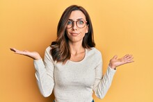 Young Brunette Woman Wearing Casual Clothes And Glasses Clueless And Confused With Open Arms, No Idea And Doubtful Face.