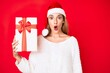 Leinwandbild Motiv Young brunette woman wearing christmas hat and holding a gift scared and amazed with open mouth for surprise, disbelief face