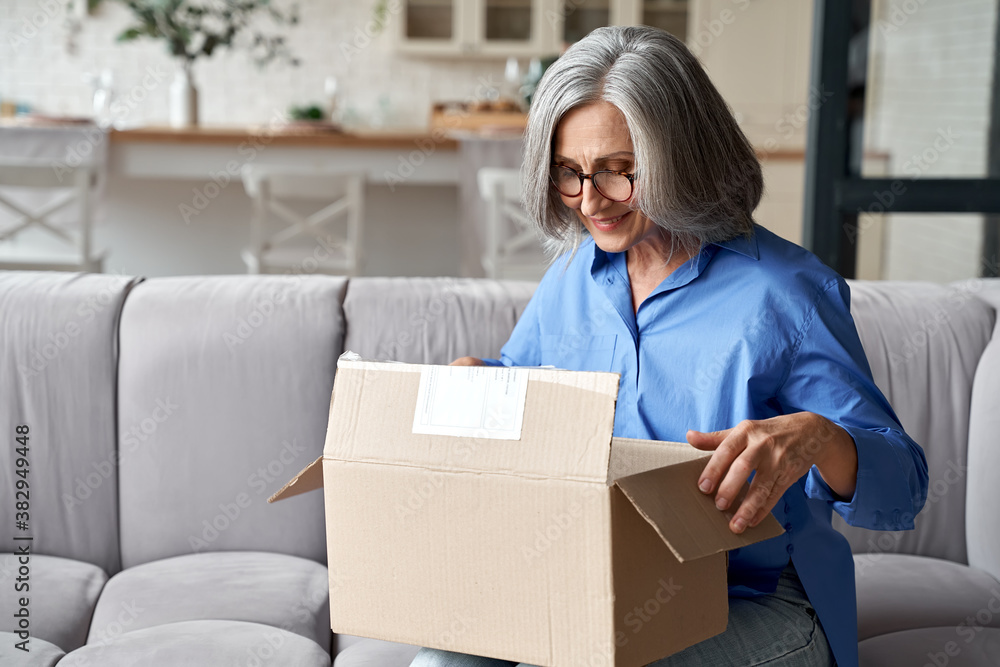 Fototapeta Smiling older adult mature woman customer unpacking parcel concept sitting at home on couch. Happy senior middle aged lady opening online store order receiving gift in postal delivery shipping box.