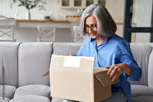 Fototapeta Smiling older adult mature woman customer unpacking parcel concept sitting at home on couch. Happy senior middle aged lady opening online store order receiving gift in postal delivery shipping box. obraz