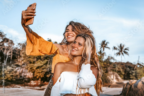 Fotografía two beautiful young stylish woman taking selfie on the beach