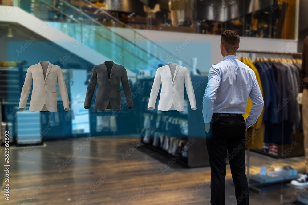 Fototapeta iot smart retail futuristic technology concept, happy man try to use smart display with virtual or augmented reality  in the shop or retail to choose select ,buy cloths and give a rating of products