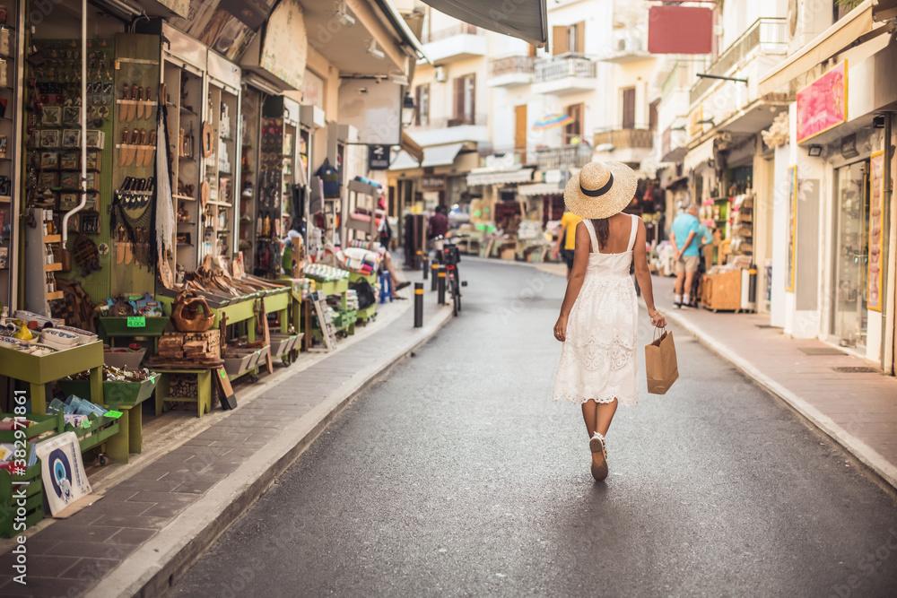 Fototapeta Rear view of woman walking on the city street
