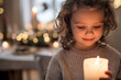 Leinwandbild Motiv Cheerful small girl indoors at home at Christmas, holding candle.