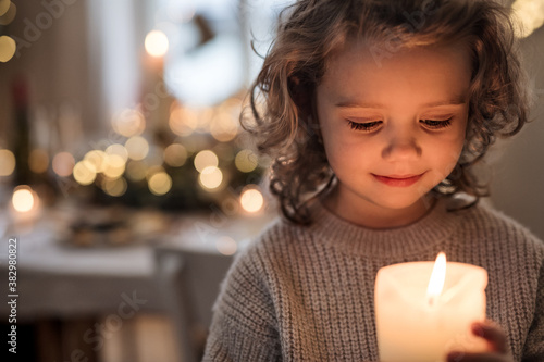 Fototapeta Cheerful small girl indoors at home at Christmas, holding candle. obraz