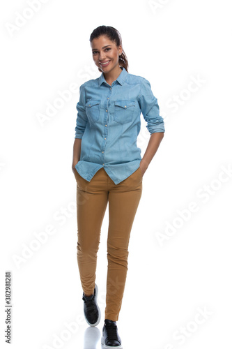 Cheerful smart casual woman smiling with both hands in pockets Wallpaper Mural