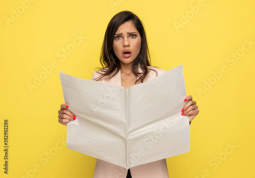 Obraz upset young woman in pink suit reading newspaper - fototapety do salonu