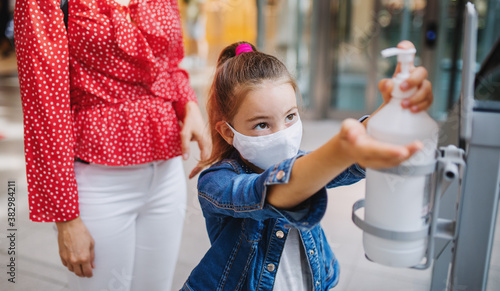 Fotografiet Mother and daughter with face mask disinfecting hands indoors in shopping center, coronavirus concept