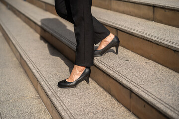 business woman with high heel shoes walking down on the stairs in city