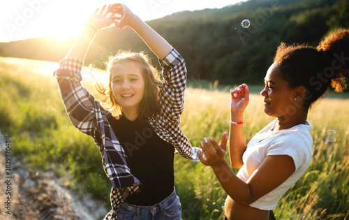 Obraz na plátně Young teenager girls friends outdoors in nature at sunset, blowing bubbles