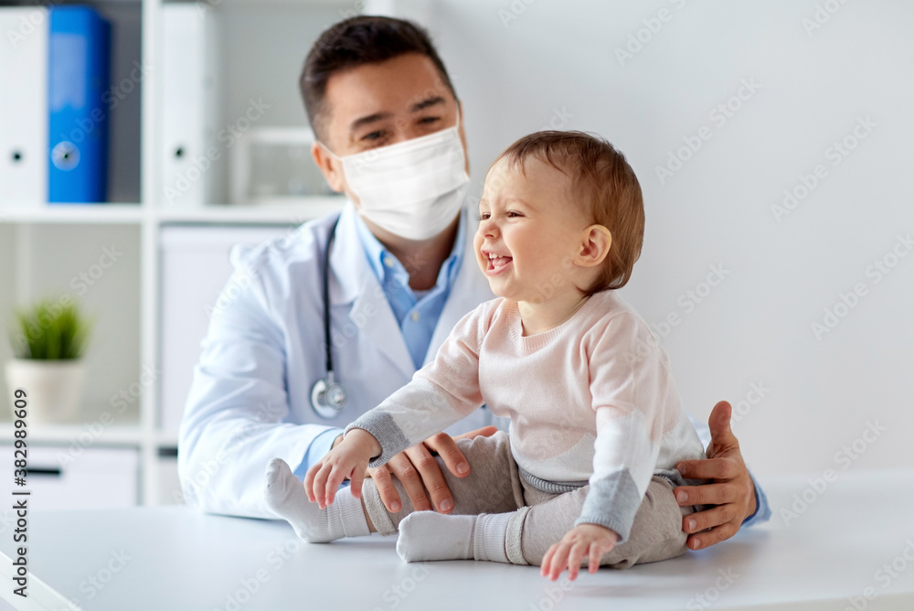 Fototapeta medicine, healtcare, pediatry and people concept - happy doctor or pediatrician wearing face protective mask for protection from virus disease with baby on medical exam at clinic