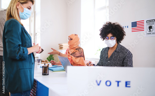 People with face masks voting in polling place, usa elections and coronavirus.