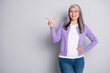 Photo portrait of positive satisfied grandmother smiling looking pointing showing at side with finger wearing jeans violet cardigan spectacles isolated on grey color background