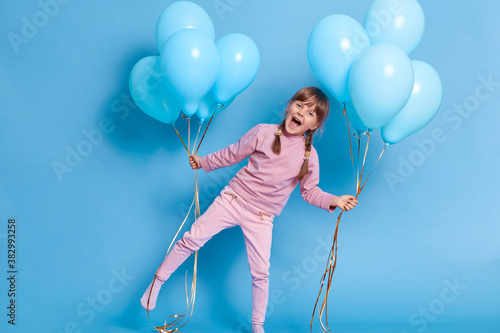 Happy laughing girl standing on one leg with widely opened mouth, girl with dark hair and pigtails holding bunches of helium balloons, posing isolated over blue background, has fun on birthday party Canvas Print