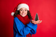 Leinwandbild Motiv Close-up portrait of her she nice attractive pretty lovely amazed cheerful girl wearing festal look holding on palm tiny festal tree Eve Noel isolated bright vivid shine vibrant red color background
